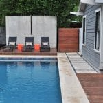 Swimming pool and deck with concrete wall in contemporary style