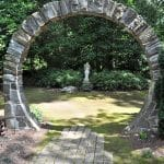 Stone moon gate and statue in the garden of Ellen Ash, in Great Falls, Virginia