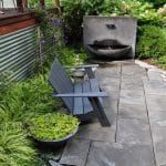 Stone patio with Loll bench and fountain in Maryland garden of designer Debbie Friedman