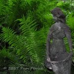 Statue of a young woman amid ferns