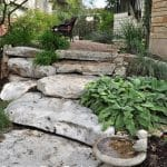 Limestone boulder steps lead up through a waterwise garden in Austin, Texas