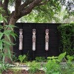 Thai rice goddess figures adorn a fence at Tanglewild Gardens in Austin, TX.