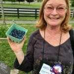 Peggy Montgomery showing off a pint of blueberries