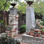 Urn-topped towers mark the entrance to a path in Jackson Broussard's Austin, Texas, garden