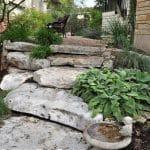 Limestone boulder steps lead up through a waterwise garden in Austin, Texas
